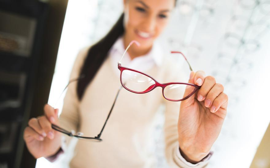 kobieta trzymająca dwie pary okularów